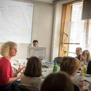 Workshopgruppen Teilnehmerinnen und Teilnehmer sitzen am Tisch und hören Teilnehmerin im roten Pullover zu. Im Hintergrund ist die Präsentation von Kiez Klima zu sehen und ein Teilnehmer sitzt hinter einem Bildschirm.