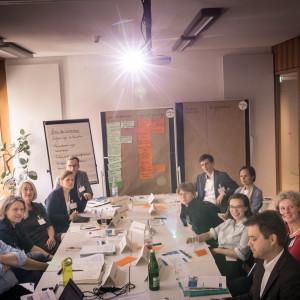 Workshopgruppenteilnehmerinnen und -teilnehmer sitzen sich gegenüber am Tisch und schauen hoch in die Kamera, die das Licht vom Beamer eingefangen hat und im Bild über der Gruppe als leuchtender Stern erscheint. Im Hintergrund stehen Moderationswände bestückt mit beschrifteten Papier. Der Tisch ist bedeckt mit Moderationsmaterilien und Getränken.