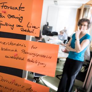 Im Vordergrund in groß sieht man zum Thema Beteiligung beschriftete, orangene Moderationskarten. Im Hintergrund steht eine Teilnehmerin im Workshopgruppenarbeitsraum vor den Arbeitstisch. Ein Teilnehmer sitzt schreibend am Tisch.