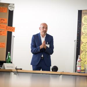 Ein Teilnehmer steht gestikulierend zwischen zwei Moderationswänden und stellt die Workshopergebnisse vor. Die Wände sind bestückt mit orangenen, gelben, blauen und grünen Moderationskarten.