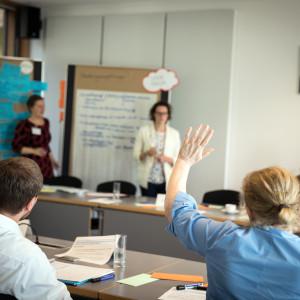 Zwei Teilnehmerinnen stehen vor zwei Moderationswänden. Die Wände sind mit Moderationsmaterialien bestückt. Im Vordergrund hebt eine Teilnehmerin in blauer Bluse die Hand zur Wortmeldung. Andere Teilnehmerinnen und Teilnehmer sitzen sich geben über am Arbeitstisch. Im Hintergrund hängt ein Bild des deutschen Bundespräsidenten.