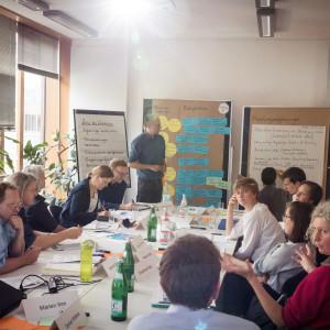 Teilnehmerinnen und Teilnehmer sitzen sich am Arbeitstisch gegenüber. Auf dem Tisch liegen Moderationsmaterialien, Unterlagen. Es stehen verteilt Getränke und ein Laptop. Im Hintergrund steht ein Teilnehmer vor den Moderationswänden. Die sitzenden Teilnehmerinnen und Teilnehmer diskutieren miteinander.