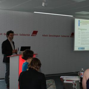 Vortragender steht am Rederpult und präsentiert im Hintergrund das Programm des Stakeholderdialoges.