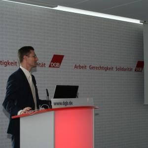 Vortragender steht am Rederpult und präsentiert im Hintergrund seitlich den Vortrag: Der politische Rahmen für Klimaanpassung in Deutschland.