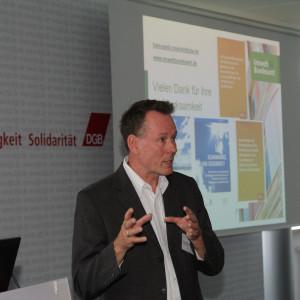 Vortragender steht am Rederpult und diskutiert gestikulierend mit den anderen Teilnehmern. Im Hintergrund ist der Abspann seiner Präsentation: Gesundheitliche Auswirkungen des Klimawandels in Deutschland
