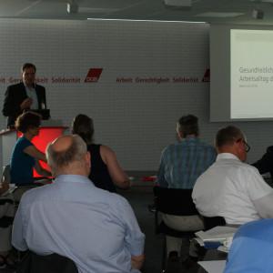 Vortragender steht am Rederpult und diskutiert gestikulierend mit den anderen Teilnehmern. Im Hintergrund ist das Startbild seiner Präsentation zu sehen.