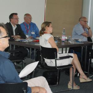 Teilnehmer sitzen im Arbeitsgruppenraum an Arbeitsgruppentischen mit dem Redner zugewandten Gesichtern.