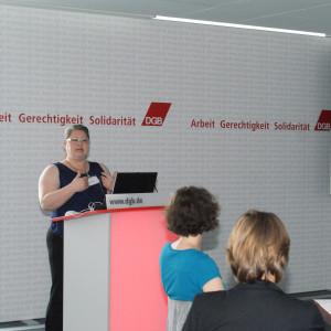 Vortragende steht am Rednerpult und trägt gestikulierend ihre Präsentation vor