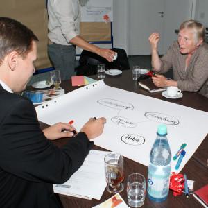 Teilnehmer sind am Gruppenarbeitstisch und diskutieren miteinander. Ein Teilnehmer schreibt Diskussionsergebnisse auf Posterpapier, welches auf dem Tisch liegt.