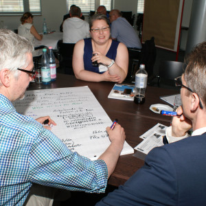 Teilnehmer sitzen im Arbeitsgruppenraum am Arbeitsgruppentisch und diskutieren miteinander.
