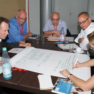 Teilnehmer sitzen im Arbeitsgruppenraum am Arbeitsgruppentisch und schauen auf das, was eine Teilnehmerin auf dem auf dem Tisch liegendes große Blatt Papier schreibt.