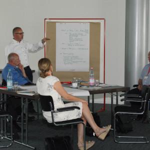 Vortragender steht an einer Moderationswand und erläutert die Arbeitsgruppenergebnisse, die dort handschriftlich angepinnt hängen.