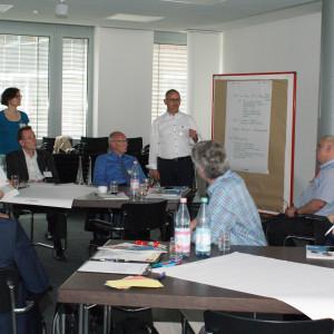 Vortragender steht an einer Moderationswand und trägt vor. Teilnehmer sitzen an den Gruppenarbeitstischen davor und hören aufmerksam zu.