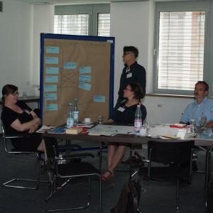 Teilnehmer steht an der Moderationswand und schaut auf die Moderationskarten. Im Vordergrund sitzen Teilnehmer am Gruppenarbeitstisch und schauen nachdenklich.