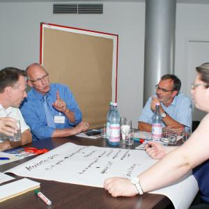 Teilnehmer diskutieren am Gruppenarbeitstisch. Eine Teilnehmerin schreibt Diskussionsergebnisse auf Posterpapier, welches auf dem Tisch liegt. Erfrischungsgetränke stehen auf dem Tisch. Ein Teilnehmer trinkt aus einem Glas Mineralwasser.