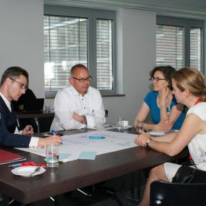 Teilnehmer diskutieren am Gruppenarbeitstisch. Ein Teilnehmer schreibt die Diskussionsergebnisse auf Posterpapier, welches auf dem Tisch liegt.