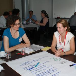 Teilnehmer sitzen am Gruppenarbeitstisch. Ein Teilnehmer steht am Tisch und legt den Stift aus der Hand, mit dem er die Diskussionsergebnisse der Diskutanten am Arbeitstisch auf das Posterpapier geschrieben hat. Die Teilnehmer schauen freundlich und lachen.