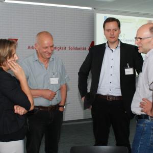 Vier Teilnehmer stehen diskutierend zusammen und schauen freundlich zueinander.
