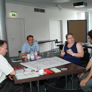 Teilnehmer sitzen diskutierend am Gruppenarbeitstisch. Auf dem Tisch liegt das beschriebene Posterpapier mit den Diskussionsergebnissen. Im Hintergrund stehen andere diskutierende Teilnehmer an einer Moderationswand.