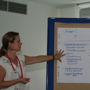 Teilnehmerin steht an der Moderationswand und zeigt auf die Ergebnisse der Arbeitsgruppe 3.