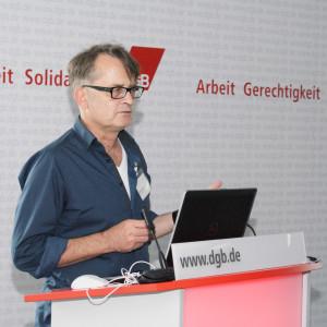 Vortragender steht am Rednerpult vor aufgeschlagenem Laptop. Im Hintergrund ist das DGB Logo zu sehen: Gerechtigkeit, Solidarität, Arbeit
