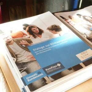 Draufsicht auf zwei Stapel der Broschüre mit dem Titel: Dialoge zur Klimaanpassung - Eine Veranstaltung zu Chancen und Risiken des Klimawandels. Auf dem Cover diskutieren gestikulierend Personen miteinander. Die Logos der Veranstalter sind ebenfalls abgebildet.