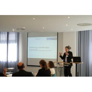 Ein Vortragender steht am Rednerpult und eröffnet gestikulierend den Dialog. Im Hintergrund erscheint das Eröffnungbild des Dialogs mit Titel und Logo.