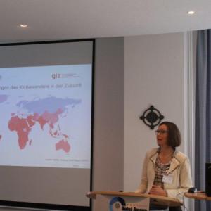 Vortragende steht am Rednerpult. Im Hintergrund ist eine Präsentationsbild in Form einer Weltkarte zu sehen.