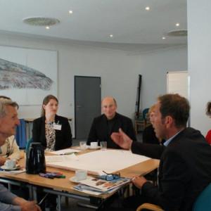 Teilnehmer sitzen diskutieren am Arbeitsgruppentisch und hören dem gestikulierenden Sprecher zu. Alle schauen freundlich drein.