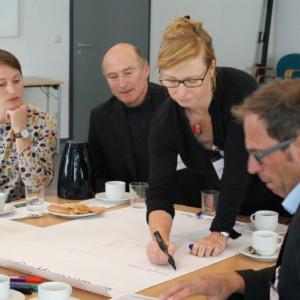 An einem Arbeitsgruppentisch steht eine Teilnehmerin und schreiben mit einem schwarzen Stift einen Beitrag auf Papier. Die anderen Teilnehmer schauen interessiertzu.
