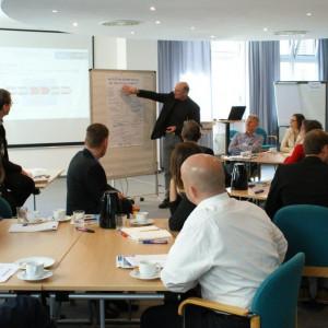 Ein Teilnehmer erklärt Gruppenarbeitsergebnisse zeigend am Flipchart bestückt mit einer handschriftlichen Grafik. Die anderen Teilnehmer sitzen an den Gruppenarbeitstischen und hören zu.