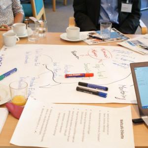 Ansicht auf einen Gruppenarbeitstisch zeigt in bunten Farben beschriebenes Papier, Stifte, ein aufgeklapptes Laptop, einen Teller mit Keksen und Gläser und Tassen mit Getränken.