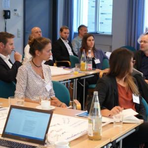 Der Blick geht hinein in den Arbeitsgruppenraum, wo die Teilnehmer an den Arbeitsgruppentischen sitzen. Ein Teilnehmer erzählt etwas. Andere Teilnehmer hören zu. Eine Teilnehmerin dreht sich dem Erzählenden zu.