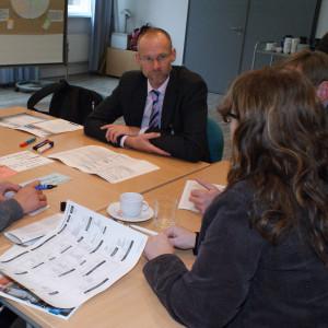 Teilnehmende sitzen am Gruppenarbeitstisch und schauen eine Teilnehmerin an. Moderationsmaterialien befinden sich auf dem Tisch sowie eine Kaffetasse und ein Getränkeglas.