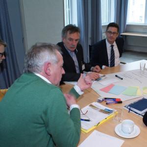 Teilnehmende sitzen an einem Gruppenarbeitstisch und hören einem Teilnehmer zu. Der Teilnehmer trägt einen grünen Pullover und gestikuliert wie bei einer Aufzählung.