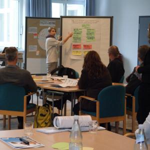 Teilnehmende trägt mithilfe einer Moderationswand vor. Sie zeigt auf die farbigen Karten und erläutert deren Bedeutung. Die anderen Teilnehmenden sitzen davor und hören zu.