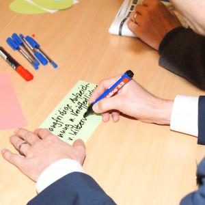 Teilnehmende beschriften farbige Moderationskarten in der Ansicht von oben sieht man die Hände. Farbige Moderationsstifte sowie eine Getränkeflasche sind ebenfalls zu sehen auf dem Gruppenarbeitstisch.
