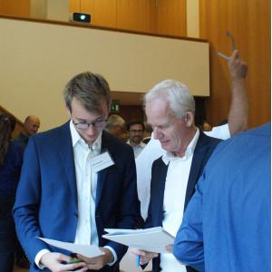 Zwei Teilnehmenden tauschen sich aus und betrachten dabei die Unterlagen in ihren Händen. Sie tragen blaue Sackos über weiße Hemden.