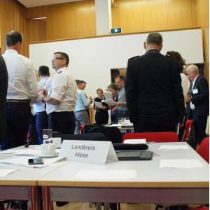 Teilnehemende stehen in lockeren Gesprächsgruppen beieinander. Sie tragen vorwiegend weiße Hemden und blaue Hosen. Im Vordergrund stehen ein Tischschild mit der Bezeichnung Landkreis Hiese.