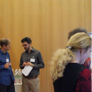 Zwei Teilnehmende stehen vor dem Getränketisch und unterhalten sich. Beide tragen Namenschilder am Hemd und halten Papiere und ein Glas Wasser in den Händen.