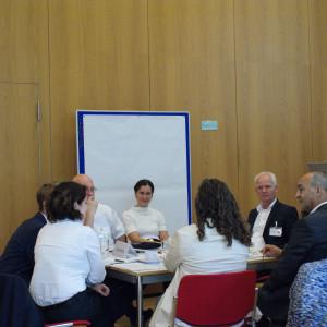 Teilnehmende sitzen an einem Gruppenarbeitstisch und hören einer Teilnehmerin zu. Im Hintergrund steht eine Pinwand mit einem großen leeren weißen Blatt bespannt.