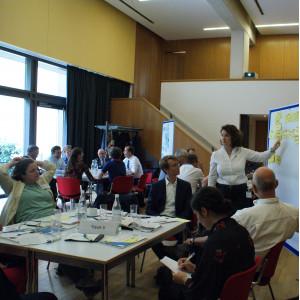 Im Vordergrund steht Gruppenarbeitstisch 3. Die Teilnehmenden sitzen um den Tisch herum und folgen den Ausführungen einer Teilnehmerin, die an der Präsentationswand zeigend steht. Im Hintergrund befindet sich eine große Fensterfront.