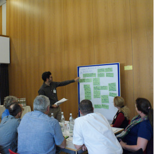 Ein Teilnehmer zeigt auf eine Präsentationswand mit grünen Moderationskarten. Im Vordergrund sitzen Teilnehmende am Gruppenarbeitstisch und hören zu.