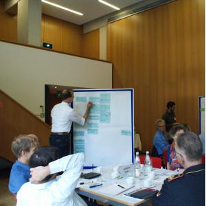 Ein Teilnehmender schreibt etwas auf eine Präsentationtswand, die mit blauen Moderationskarten bestückt ist. Im Raum sitzen alle Teilnehmenden an ihren Gruppenarbeitstischen.