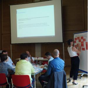 Teilnehmende präsentiert an Moderationswand mit roten Moderationskarten. Die anderen Teilnehmenden sitzen nachdenklich am Gruppenarbeitstisch. Im Hintergrund ist eine Präsentation eingblendet.
