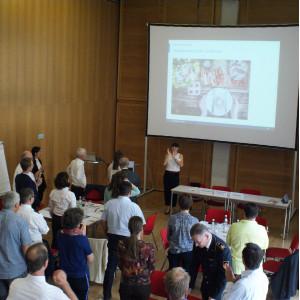 Alle Teilnehmenden stehen im Raum und folgen der Präsentation einer Teilnehmerin, die vor der Leinwand steht. Manche Teilnehmende applaudieren. Teile der Präsentationswände mit den farbigen Moderationskarten stehen am Rand verteilt