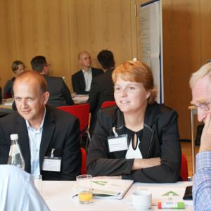 Zwei Teilnehmende sitzen nebeneinander am Gruppenarbeitstisch und hören anderen Teilnehmern zu. Im Hintergrund sitzen andere Teilnehmer am anderen Gruppenarbeitisch. Neben diesem Gruppenarbeitstisch steht eine Moderationswand.