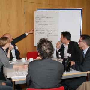 Teilnehmer sitzen am Gruppenarbeitstisch. Ein Teilnehmer zeigt mit ausgestrecktem Arm auf beschriftetes Papier an Moderationswand im Hintergrund.