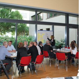 Teilnehmer sitzen an Gruppenarbeitstischen im Raum vor einer großen Fensterfront. Eine Teilnehmerin schreibt im Hintergrund Text auf Papier an Moderationswand.