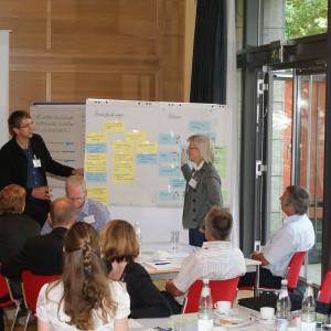 Zwei Teilnehmer stehen an Moderationswand im Dialog miteinander. An der Moderationswand hängen farbige Moderationskarten. Auf der rechten Seite steht die Tür von der Fensterfront offen. Zuhörer sitzen im Vordergrund an Gruppenarbeitstischen.